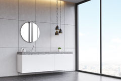 Side view of a bathroom sink with round mirror on tiled wall, co. Corner of a bathroom interior with a tiled wall, concrete floor, a round mirror and a long sink royalty free stock photo