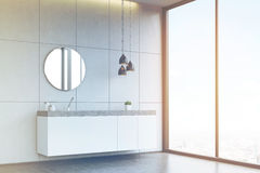 Side view of a bathroom sink with round mirror on tiled wall, co. Corner of a bathroom interior with a tiled wall, concrete floor, a round mirror and a long sink Stock Photography