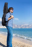 Side view of bearded man with guitar in backpack on coastline Royalty Free Stock Photo