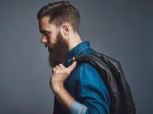 Side view on bearded man holding black jacket Royalty Free Stock Image