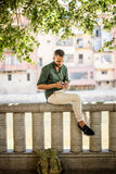 Side view of bearded man sitting on fence under trees Royalty Free Stock Photography