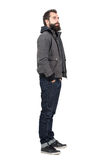 Side view of bearded man wearing jacket over hooded shirt looking away Stock Photos