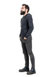 Side view of bearded punker or hipster with hands in pockets looking up. Full body length portrait isolated over white studio background Stock Images