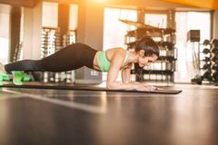 Adult woman performing plank in gym stock images
