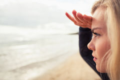 Side view of a beautiful blond shielding eyes at beach Royalty Free Stock Image