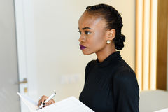 Side view of beautiful business woman with bright violet lips holding white notepad and pen in light office Royalty Free Stock Photos