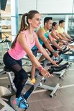 Beautiful fit woman smiling during cardio workout at indoor cycling cla Royalty Free Stock Images