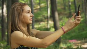 Side view of beautiful fitness girl holding phone with both hands, fixing hair and posing for selfie photo. Beautiful fitness girl using mobile phone outdoors stock video footage