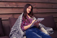 Side view of beautiful girl in casual clothes under blanket maki Stock Photography