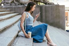 Side view of beautiful girl holding paper cup and using smartphone while sitting. On stairs royalty free stock images