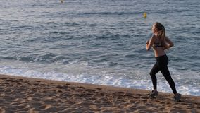 Blonde female runner exercising on sandy beach. Side view of beautiful long haired fitness woman jogging along sea coast on background of seascape. Slim female stock video footage
