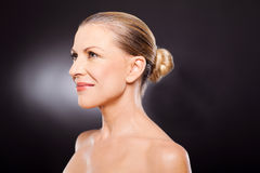 Mature woman side. Side view of a beautiful mature middle aged woman on black background Stock Image