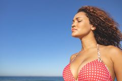 Woman in bikini standing with eyes closed on the beach. Side view of beautiful mixed race woman in bikini standing with eyes closed on the beach royalty free stock photo
