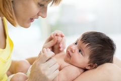 Side view of beautiful mother and her infant baby looking at each other, spending time together at home stock photo