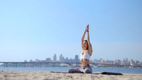 Portrait of a beautiful relaxed young woman sitting in lotus pose at the beach with sea and city background. womans stock video
