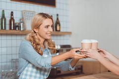 Side view of beautiful smiling waitress in apron giving waitress holding disposable coffee cups. To buyer stock photos