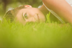 Side view of beautiful smiling woman lying on grass Royalty Free Stock Image