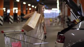 Pretty female putting purchases in car trunk. Side view of beautiful woman with long blonde hair putting purchases in paper bags from shopping cart in car trunk stock footage