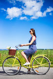 Side view of beautiful woman riding retro bicycle in countryside Stock Images