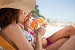 Side view of a beautiful woman sipping her cocktail accompanied Stock Photos