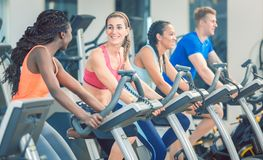 Side view of a beautiful woman smiling while cycling at the gym. Brunette beautiful women smiling while cycling on a modern fitness bicycle during group spinning royalty free stock photos