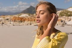 Woman standing with eyes closed on the beach. Side view of a beautiful woman standing with eyes closed and posing on the beach stock photos