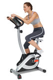 Side view of a beautiful woman on stationary bike Royalty Free Stock Photos