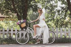 Side view of beautiful young bride in wedding dress riding bicycle. And looking away royalty free stock image