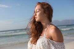 Young Caucasian woman with eyes closed standing on the beach. Side view of beautiful young Caucasian woman with eyes closed standing standing on the beach. She royalty free stock photo