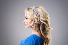 Side view of beautiful, young lady wearing sapphire coronet and earrings over grey background Stock Images