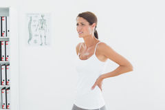 Side view of a beautiful young woman with back pain Stock Photo