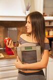 Side view of beautiful young woman holding weight scale. Royalty Free Stock Photo