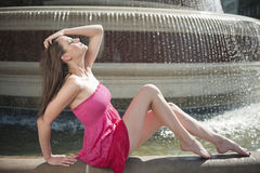 Side view of beautiful young woman in pink dress sitting by water fountain Stock Photo