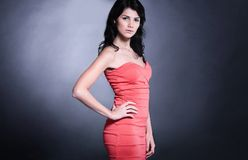 Side view.beautiful young woman in a red dress. isolated on blac Stock Images