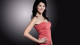 Side view.beautiful young woman in a red dress. isolated on blac Stock Photos