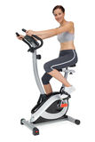 Side view of a beautiful young woman on stationary bike Royalty Free Stock Images