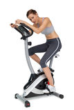 Side view of a beautiful young woman on stationary bike Stock Image