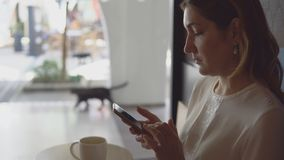 People on holiday in warm countries. Side view - beautiful young woman typing text on smartphone sitting at table in cafe on the background of large window stock video