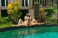 side view of beautiful young women in bikini sitting back to back stock image