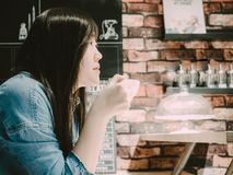 Side view of beauty asian hipster girl 25s to 35s with blue ja. Cket jean during hold white coffee cup and drink with soft focus coffee shop and bar background Royalty Free Stock Images