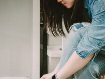 Side view from beauty hipster woman in jean cloth and blue smart. Watch on arm tie her shoelace with soft focus background Stock Photography