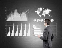 Side view of a bespectacled businessman looking at graphs stock images