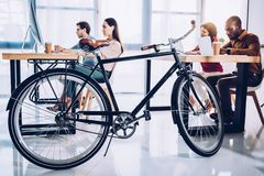 Side view of bicycle and multicultural business people working. In office royalty free stock image