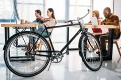 Side view of bicycle and multicultural business people working. In office royalty free stock photography