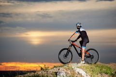 Side view of biker on mountain bike at top of rock restingwit blurred background of the sunset sky stock image