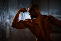 Side view of black african american fitness model showing muscles in studio background Royalty Free Stock Images