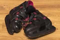 Side view black ice skates on wooden. Background Royalty Free Stock Photography