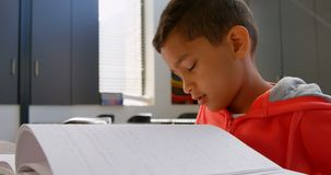Side view of blind Asian schoolboy hand reading a braille book in classroom at school 4k stock video footage