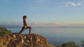 Side view blond girl does yoga asanas on cliff at sunlight. Side view young slim girl does yoga asanas on high rocky cliff against boundless azure ocean at stock video footage