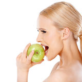 Side view of blond woman  she bites an apple Royalty Free Stock Photo